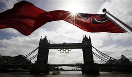A flag on the back of a river boat flutters above Tower Bridge after the Olympic Rings were lowered into position for display from the walkways in central London, June 27, 2012. The London 2012 Olympic games will begin on July 27. REUTERS/Andrew Winning OLYMPICS)