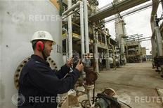 A worker adjusts the valve of an oil pipe at Zawiya oil refinery in Zawiya 57km (35 miles) west of Tripoli April 11, 2012. REUTERS/Ismail Zitouny