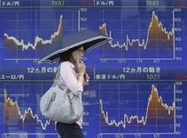 Женщина проходит мимо информационного табло в Москве, 29 июня 2012 года. Евро стабилизировался после падения до двухлетнего минимума к доллару, вызванного отсутствием надежд на плодотворный исход заседания министров финансов еврозоны, которое состоится в понедельник. REUTERS/Yuriko Nakao