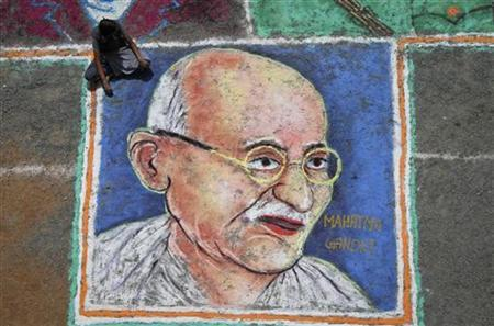 A student sits next to a painting of Mahatma Gandhi as part of Independence Day celebrations at the Velammal Vidyalaya high school in Chennai in this August 13, 2011 file photo. REUTERS/Babu/Files