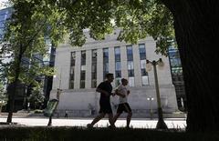 Joggers run past the Bank of Canada building in Ottawa June 5, 2012. REUTERS/Chris Wattie