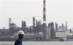 Рабочий около фабрики в промышленной зоне Кэйхин в японском городе Кавасаки, 31 мая 2011 года. Данные крупнейших азиатских экспортеров показали признаки замедления экономик, что является сигналом дальнейшего снижения мирового спроса, в то время как чиновники Федрезерва США высказались за смягчение монетарной политики (QE3) для усиления роста. REUTERS/Toru Hanai