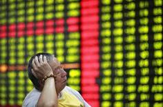 Инвестор сидит перед информационным табло в брокерском доме в Хубэй (Китай), 4 июня 2012 года. Азиатские фондовые рынки снизились из-за более слабого, чем ожидалось, показателя импорта в Китае в июне. REUTERS/Stringer
