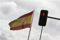 Испанский флаг развивается около светофора в центре Мадрида, 27 апреля 2012 года. Премьер-министр Испании Мариано Рахой объявил в среду о новых налогах и сокращении расходов ради уменьшения дефицита бюджета на 65 миллиардов евро к 2014 году. REUTERS/Andrea Comas