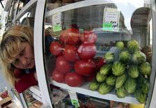 Женщина продает овощи в киоске в Москве, 9 июня 2011 года. Инфляция в РФ замедлилась с 3 по 9 июля 2012 года до 0,3 процента с 0,5 процента неделей ранее на фоне сокращения темпов роста цен на овощи и фрукты, а с начала месяца потребительские цены выросли на 0,8 процента из-за повышения тарифов на услуги ЖКХ, сообщил Росстат. REUTERS/Alexander Natruskin
