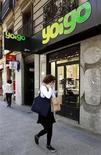 <p>Foto de archivo de una mujer junto a un tienda de la firma Yoigo en Madrid, abr 26 2011. El grupo nórdico Teliasonera prepara la venta de su unidad española de telefonía móvil Yoigo, un negocio que superaría los 1.000 millones de euros (1.227 millones de dólares) y que puede atraer el interés de la mexicana América Móvil, la británica Vodafone y France Telecom, dijeron fuentes el miércoles. REUTERS/Andrea Comas</p>