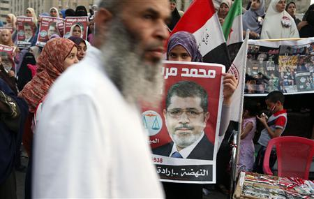 A supporter holds a poster of Egypt's President Mohamed Mursi at Tahrir square in Cairo July 10, 2012. REUTERS/Asmaa Waguih