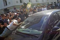 Off-duty police officers and fire fighters protesting over government austerity measures are held back by police officers as they shout at the driver of a vehicle exiting the Parliament building in Madrid July 12, 2012. REUTERS/Juan Medina