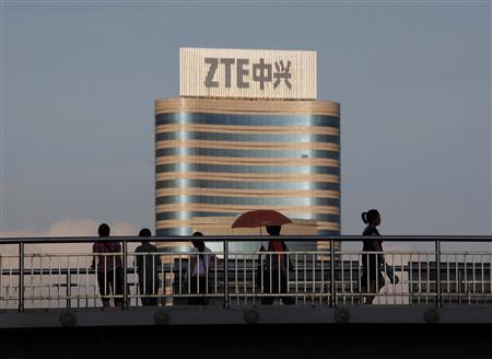 Passersby walk along a footbridge in front of the ZTE building in Nanshan Hi-Tech Industrial Estate, in the southern Chinese city of Shenzhen, in this June 9, 2011 file photo. The FBI has opened a criminal investigation into ZTE Corp over the Chinese company's sale of banned U.S. computer equipment to Iran and its alleged subsequent attempts to cover it up and obstruct a Department of Commerce probe, the Smoking Gun website reported. The federal investigations stem from a Reuters report in March that Shenzhen, China-based ZTE, a telecommunications equipment maker, had sold Iran's largest telecom firm a powerful surveillance system capable of monitoring landline, mobile and Internet communications, according to interviews and contract documents. REUTERS/Bobby Yip/Files