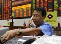 Трейдер говорит по телефону на бирже в Маниле, 7 мая 2012 года. Азиатские фондовые рынки выросли, так как ВВП Китая во втором квартале совпал с прогнозами. REUTERS/Cheryl Ravelo