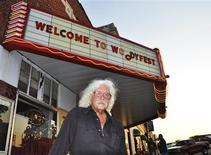Arlo Guthrie stands outside Okemah's refurbished movie theater that hosts Woodyfest, the annual folk festival that honors his father, Woody Guthrie in Okemah, Oklahoma July 11, 2012. For a man who has been dead since 1967, it has been a good year for folk singer Guthrie, who would have turned 100 on July 14, 2012. New books have been published, more Guthrie songs have been released and in the small Oklahoma town where he was born, nobody wants to burn him in effigy for his politics. Photo taken July 11, 2012. REUTERS/Steve Olafson