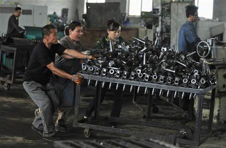 Workers push a cart carrying automobile components at a car parts plant in Shenyang, Liaoning province July 9, 2012. REUTERS/Stringer