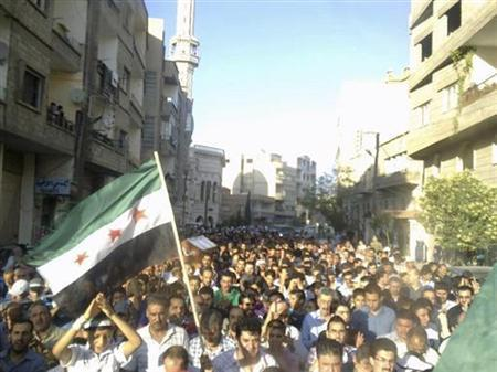 A resident holds a Syrian opposition flag as others carry the coffin of Muhammad Barakat, whom protesters say was killed by forces loyal to Syria's President Bashar al-Assad, during his funeral at Yabroud near Damaascus July 15, 2012. REUTERS/Shaam News Network/Handout