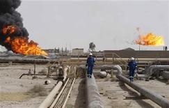 Рабочие на нефтяном месторождении Румайла в Басре, 23 мая 2011 года. Британская Premier Oil PLC объединяется с российской Башнефтью для разработки иракского нефтяного Блока 12, сообщил официальный представитель Ирака в воскресенье. REUTERS/Atef Hassan