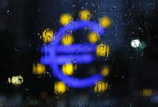 Символ евро сквозь стекло во время дождя во Франкфурте-на-Майне, 13 июля 2012 г. Курс евро снижается на фоне опасений за долговой кризис еврозоны и роста доходности периферийных гособлигаций. REUTERS/Alex Domanski