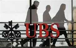 People walk behind the logo of Swiss bank UBS in Zurich in this February 7, 2012 file photo.REUTERS/Arnd Wiegmann/Files