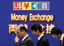 Офисные работники проходят мимо вывески пункта обмена валют в Сеуле, 12 марта 2009 года. Евро стабилен к доллару, так как глава ФРС США Бен Бернанке во вторник не исключил возможность дополнительного смягчения политики. REUTERS/Lee Jae-Won