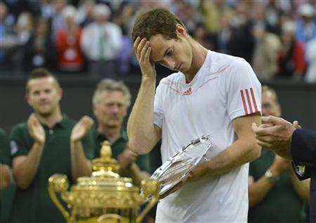 Andy Murray of Britain holds his runners-up trophy after being defeated by Roger Federer of Switzerland in their men's singles final tennis match at the Wimbledon Tennis Championships in London July 8, 2012. REUTERS/Toby Melville