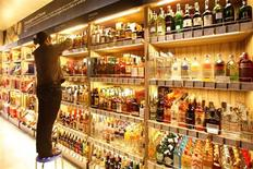 An employee arranges bottles of whisky at a supermarket in Shanghai March 9, 2011. REUTERS/Aly Song