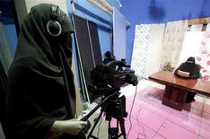 "A video woman records a program in a studio of a new TV channel which is being managed and run exclusively by women who wear the full veil, to be launched this weekend, in Cairo July 19, 2012. In an age of new freedoms in the post-Hosni Mubarak Egypt, niqab-wearing women long oppressed socially and politically are hoping for a new place in society. Though Egypt is a deeply conservative and predominantly Muslim society, niqab wearers have cited discrimination in the job market, education and elsewhere. A new TV channel being managed and run exclusively by women who wear the full veil, to be launched this weekend on the first day of the Islamic fasting month of Ramadan, hopes to let people know ""that there are successful women wearing niqab"". REUTER/Mohamed Abd El Ghany"