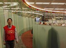 Трейдер идет по торговому залу биржи в Гонконге, 2 марта 2011 года. Азиатские фондовые рынки завершили торги пятницы и неделю разнонаправлено под влиянием локальных факторов. REUTERS/Bobby Yip