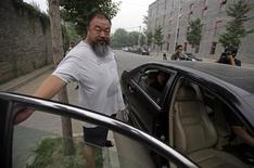 Chinese dissident artist Ai Weiwei (L) closes the door of a car as his wife Lu Qing (in car) leaves for the courthouse before his verdict hearing in Beijing, July 20, 2012.REUTERS/Petar Kujundzic