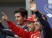Fernando Alonso comemora pole position no GP da Alemanha ao lado dos pilotos Mark Webber e Sebastian Vettel. Desafiando um clima atroz, o bicampeão mundial Fernando Alonso, da Ferrari, arrebatou a pole position do Grande Prêmio de Fórmula 1 da Alemanha neste sábado. 21/07/2012 REUTERS/Ralph Orlowski
