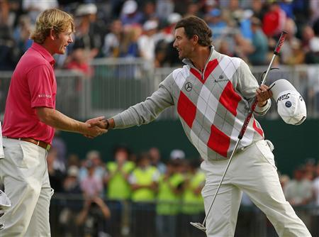 Brandt Snedeker of the U.S. (L) shakes hands with Adam Scott of Australia on the 18th green as they finish their third round of the British Open golf championship at Royal Lytham & St Annes, northern England July 21, 2012. REUTERS/Brian Snyder