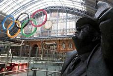 Anéis olímpicos e estátua de John Betjeman são vistos na Estação Internacional St Pancras em Londres. Depois de semanas de manchetes negativas, os organizadores da Olimpíada reagiram neste domingo dizendo que as críticas a erros de planejamento e custos estão sendo superadas pelo entusiasmo popular à medida que a cerimônia de abertura se aproxima. 22/07/2012 REUTERS/Neil Hall