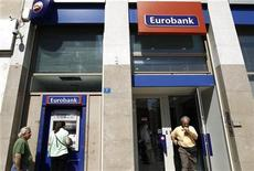 A woman makes a transaction at an ATM of a Eurobank branch in Athens September 23, 2011. REUTERS/Yiorgos Karahalis