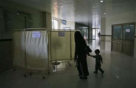 A woman walks in a hallway with her child as she arrives for treatment at the Tahir Heart Institute of the Ahmadi community in Chenabnagar of Punjab's Chiniot District July 2, 2011. REUTERS/Stringer