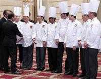 """France's President Francois Hollande (L) shakes hands with Chinese chefs Hou Fang (2ndL) and Zhao Hoang Liang (3rd L) during a reception of the """"Club des Chefs des Chefs"""" (Club of Leaders' Chefs) at the Elysee Palace in Paris, July 24, 2012, following the International meeting in France. REUTERS/Jacques Demarthon/Pool"""