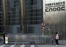 A woman walks past the entrance of the headquarters of China National Offshore Oil Corp (CNOOC) in Beijing in this September 23, 2010 file photograph. REUTERS/Petar Kujundzic/Files