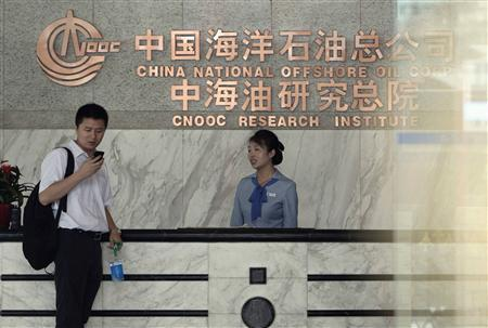 The man stands at the front desk of the headquarters of China National Offshore Oil Corp (CNOOC) in Beijing July 25, 2012. When Canada's Nexen Inc fired its CEO in January, an oil giant on the other side of the world sprang into action. Nexen had been on the wish list of Chinese state oil company CNOOC Ltd for five years. By the Chinese New Year later that month, CNOOC had hired BMO Capital Markets and Citigroup Inc as financial advisers, according to these sources. That kicked off negotiations culminating on Monday with a deal to buy Nexen for $15.1 billion, the biggest foreign acquisition ever by a Chinese company. REUTERS/Jason Lee