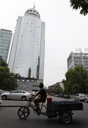 A man rides a tricycle past the China National Offshore Oil Corp (CNOOC) headquarters building in Beijing July 25, 2012. When Canada's Nexen Inc fired its CEO in January, an oil giant on the other side of the world sprang into action. Nexen had been on the wish list of Chinese state oil company CNOOC Ltd for five years. By the Chinese New Year later that month, CNOOC had hired BMO Capital Markets and Citigroup Inc as financial advisers, according to these sources. That kicked off negotiations culminating on Monday with a deal to buy Nexen for $15.1 billion, the biggest foreign acquisition ever by a Chinese company. REUTERS/Jason Lee