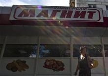 Женщина проходит мимо супермаркета Магнит в Москве, 24 июля 2012 года. Крупнейший по числу магазинов российский ритейлер Магнит обогнал конкурентов с быстроразвивающихся рынков, став пятым по капитализации продуктовым ритейлером в мире после удачного отчета. REUTERS/Maxim Shemetov
