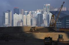 Bulldozers work on reclaimed land in Hong Kong in this February 23, 2009 file picture. Hong Kong's main shopping district is gaining on New York's 5th Avenue for the title of world's most expensive retail zone as rents rise by 35 percent a year, pushing chains such as H&M out to the cheaper suburbs. Space has always been at a premium in Hong Kong, an island-city, like Manhattan, where developers plant high-rises on every available inch. Retail rents in prime shopping areas are rising more rapidly here than in New York, London or Paris. Picture taken February 23, 2009. REUTERS/Bobby Yip