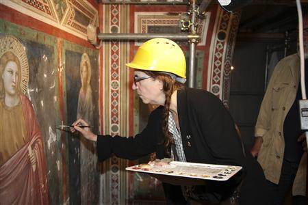 Rocker Patti Smith helps restorers clean a fresco by Giotto during her visit to the Basilica of St Francis in Assisi July 25, 2012. The singer, whose latest album was inspired by St Francis, meditated before the tomb of the saint, who is a symbol of peace, and ate a simple meal with the monks in their refectory. REUTERS/Sanfrancesco.org/handout