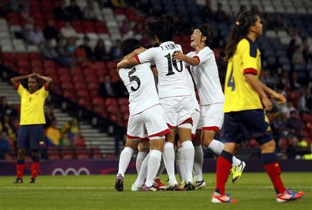 North Korea's Yun Song-Mi (2nd L) and Yun Hyon-Hui celebrate with other players after Kim Song-Hui scored a goal against Colombia as Colombia's players react during their women's Group G football match at the London 2012 Olympic Games in Hampden Park, Glasgow, Scotland July 25, 2012. REUTERS/David Moir
