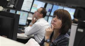 Трейдер следит за ходом торгов на бирже во Франкфурте-на-Майне, 24 июля 2012 года. Европейские акции снижаются на фоне противоречивых квартальных отчетов компаний и ожиданий новых стимулирующих мер центробанка США. REUTERS/Alex Domanski
