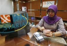 Служащая Bank Negara Indonesia пересчитывает рупии в Джакарте 30 января 2009 года. Первый в бывшем СССР выпуск Банком развития Казахстана исламских облигаций - сукук - на $75 миллионов может стать катализатором новых эмиссий в крупнейшей экономике Центральной Азии, сказали в четверг банкиры и чиновники. REUTERS/Crack Palinggi