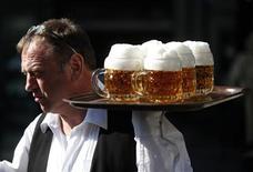 Официант разносит кружки с пивом в ресторане в Вене, 20 марта 2012 года. Футбольная лихорадка помогла SABMiller нарастить квартальные продажи в Европе, превысившие ожидания аналитиков. REUTERS/Herwig Prammer