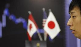 Трейдер следит за валютными курсами в Токио, 13 октября 2010 года. Азиатские фондовые рынки выросли в надежде на новые меры Европейского Центробанка. REUTERS/Yuriko Nakao
