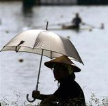A spectator watching the World Rowing Championships wears a traditional Japanese hat and holds an umbrella while sitting in the hot summer sun in Gifu, Japan August 29, 2005. REUTERS/Andy Clark AC/SA