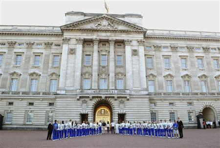 Britain's Prince William, along with Catherine, Duchess of Cambridge and Prince Harry are joined by members of the Team GB Ambition Programme as they wait for Olympic torch bearer Wai-Ming Lee to hand over the flame to John Hulse (centre, R) during a visit to Buckingham Palace in London July 26, 2012. REUTERS/Ian West/Pool