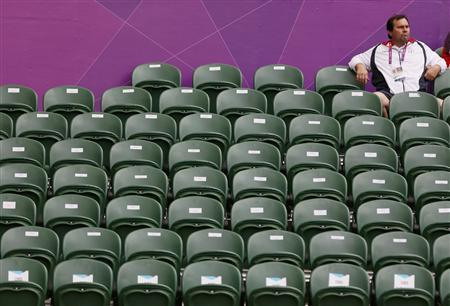 A spectator sits amid empty seats at the All England Lawn Tennis Club during the women's singles match between Denmark's Caroline Wozniacki and Great Britain's Anne Keothavong at the London 2012 Olympics Games July 28, 2012. REUTERS/Stefan Wermuth