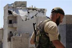 A member of the Free Syrian Army walks past a destroyed building in Azzaz, Aleppo province July 17, 2012. Picture taken July 17, 2012. REUTERS/Abdo