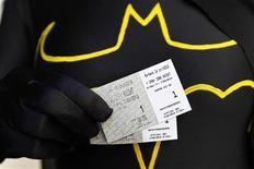 """Женщина показывает билеты на фильм """"Темный рыцарь: Возрождение легенды"""" в Бербанке (штат Калифорния), 20 июля 2012 года. Новый фильм о Бэтмене """"Темный рыцарь: Возрождение легенды"""" заработал $64,1 миллиона в США и Канаде и сохранил за собой лидерство в прокате, несмотря на бойню на показе фильма в штате Колорадо и старт Олимпиады-2012 в Лондоне. REUTERS/Fred Prouser"""