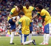 Oscar comemora terceiro gol da seleção brasileira com companheiros de equipe em partida das Olimpíadas de Londres. O técnico Mano Menezes convocou a base da seleção brasileira que disputa a Olimpíada de Londres para o amistoso contra a Suécia, em Estocolmo, no dia 15 de agosto. 29/07/2012 REUTERS/Andrea Comas