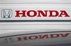 Логотип Honda Motor Co отражается на крыше автомобиля на юге Токио, 31 июля 2012 года. Операционная прибыль Honda Motor Co составила в апреле-июне 2012 года 176 миллиардов иен ($2,25 миллиарда), показав меньший рост, чем ожидалось рынком, из-за укрепления иены. REUTERS/Yuriko Nakao